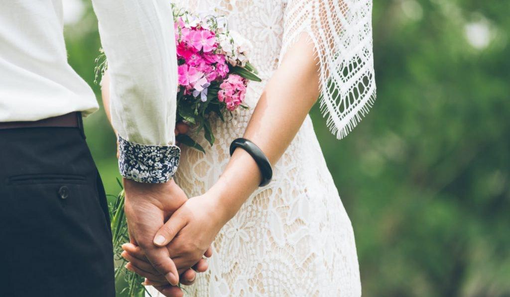 Braut im Boho-Kleid hält die Hand des Bräutigams